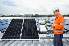 Engineer maintenance solar panel equipment on factory roof royalty free stock photo