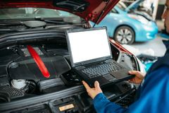 Engineer makes computer diagnostics of car engine. Engineer with laptop makes computer diagnostics of the car engine in auto-service. Vehicle wiring inspection stock image