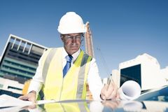 Senior foreman in glasses doing his job at building area on car Royalty Free Stock Photography