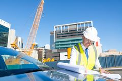 Senior foreman in glasses doing his job at building area on car hood Stock Photography