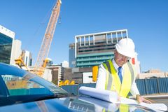Senior foreman in glasses doing his job at building area on car hood Stock Photo