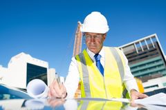 Senior foreman in glasses doing his job at building area on car hood Royalty Free Stock Image