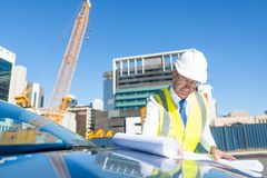 Senior foreman in glasses doing his job at building area on car hood Royalty Free Stock Photos