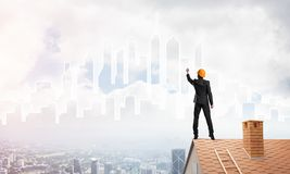 Man architect draw silhouette of modern city on blue sky. Mixed media Royalty Free Stock Image