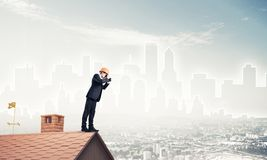 Engineer man standing on roof and looking in binoculars. Mixed m Stock Images