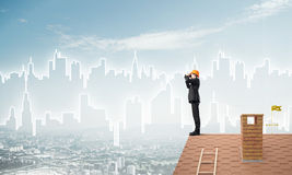 Engineer man standing on roof and looking in binoculars. Mixed media Stock Photography