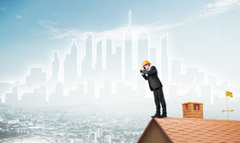 Engineer man standing on roof and looking in binoculars. Mixed media Stock Photos