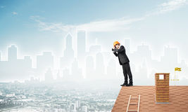 Engineer man standing on roof and looking in binoculars. Mixed media Royalty Free Stock Photos