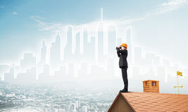 Engineer man standing on roof and looking in binoculars. Mixed media Stock Photo