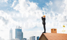 Engineer man standing on roof and looking in binoculars. Mixed media. Young businessman in suit and helmet on roof edge in search of something new. 3D rendering Royalty Free Stock Photo