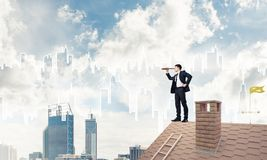 Engineer man standing on roof and looking in spyglass. Mixed med Stock Photos