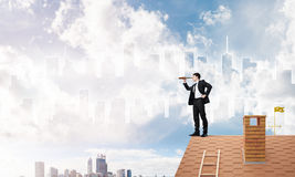 Engineer man standing on roof and looking in spyglass. Mixed media. Young businessman in suit on roof edge. 3D rendering Royalty Free Stock Image