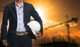 Engineer man standing with white safety helmet against beautiful. Dusky sky with building construction site use for engineering and construction industrial Stock Photography