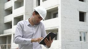 Engineer man with tablet talking on mobile phone and checking building technology process. Construction site engineer with tablet talking on mobile phone stock video