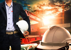 Engineer man with white safety helmet standing against working t Stock Image