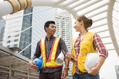 Engineer man and woman in town. Happy Engineer team of Handsome Asian men and beauty American women look at each other to encourage . International joint venture Royalty Free Stock Images