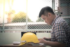 Engineer manager. Feel so serious during working document about progress of work schedule on the construction job site Royalty Free Stock Photo
