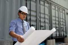 Engineer manager read blueprint plan. Senior Asian Engineer manager, 40-50 years old man, reading paper blueprint project plan  near container box at Royalty Free Stock Photography