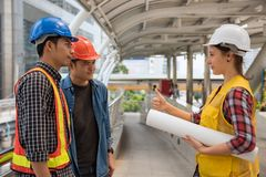 Engineer manager thumb up to team. American Engineer manager thumb up or cheer up to her engineering team in modern city. Teamwork concept for heavy construction Stock Photography