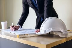 Engineering helmet on Businessman table. Engineer manager white helmet with engineering manager writing blueprint paper on office table with copy space for text Stock Photo