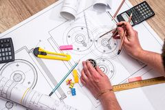 Engineer measures the dimensions. Of the drawing Royalty Free Stock Photo