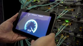 IT engineer measures network speed with a tablet computer in hand. LEDs blink. On background server racks. There is vibration in t