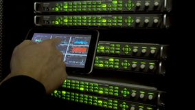 IT engineer measures network speed with a tablet computer in hand. LEDs blink. On background server racks. There is vibration in t stock footage