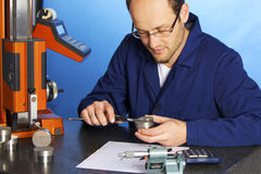 Engineer measuring with caliper. Young male engineer in blue overall measuring a metal part with caliper, isolated on blue background Stock Photo