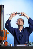 Engineer measuring with caliper against light. Young male engineer in blue overall measuring a metal part with caliper holding it against the light,  isolated on Royalty Free Stock Photos