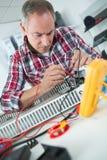 Engineer measuring multimeter panel board. Man royalty free stock photography