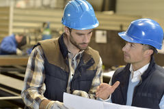 Engineer with mechanical worker checking on production quality Royalty Free Stock Images