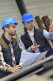 Engineer and mechanical worker discussing production Royalty Free Stock Photo