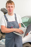 Engineer of mechanics with a laptop near a car. In a garage Royalty Free Stock Images