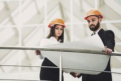 Engineer man and woman in hardhats discussion Stock Photography
