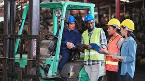 Engineer men workers or technical holding tablet and discuss together on process of work. Other women worker walk pass the team.