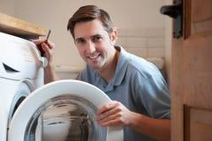 Engineer Mending Domestic Washing Machine. Engineer Mends Domestic Washing Machine Stock Photos