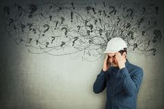 Engineer mess in head. Stressed engineer holding arms to head eyes closed feeling exhausted. Headache, anxiety and health problems as sketch mess in his head stock image