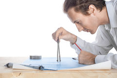 Engineer middle-aged white man examines blueprint Stock Images