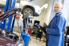 Engineer with notebook during car air conditioner refilling. Caucasian mechanic engineer with notebook during car air conditioner refilling on automobile service Stock Photography