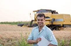 Engineer with notebook and combine harvester in field. Happy young farmer engineer with notebook standing on wheat field while combine harvester working in stock image