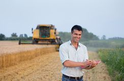 Engineer with notebook and combine harvester Royalty Free Stock Photo