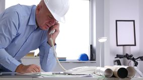 Engineer in office room talking to cellphone and making technical calculations