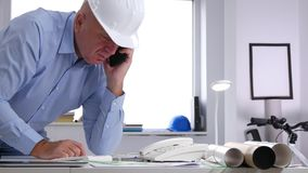 Engineer in Office Talking Business t a Cell Phone Looking to Technical Plans