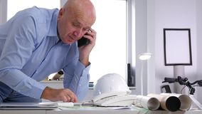 Engineer in office talking business t a cell phone looking to technical plans.  stock video