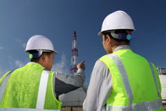 Engineer oil refinery. Two engineer discussion about plan working on location site Royalty Free Stock Images