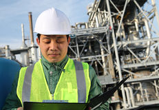 Engineer oil refinery. Engineer standing in front of a large oil refinery Stock Photo