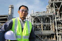 Engineer oil refinery. Engineer standing in front of a large oil refinery and blue sky background Royalty Free Stock Photography