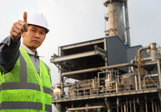 Engineer oil refinery. Industrial engineer with thumbs up and large oil refinery background Stock Photos
