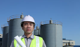 Engineer of oil refinery. Standing on location site Stock Photography