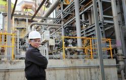 Engineer oil refinery. Engineer standing beside pipeline inside oil refinery Royalty Free Stock Photo